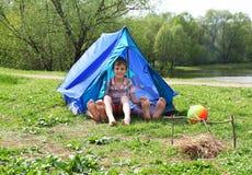 Von den Zelten auf Wiese haften Fahrwerkbeine heraus und Junge Lizenzfreie Stockbilder