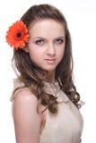 Von der jungen schönen Frau mit orange Blume Lizenzfreies Stockfoto
