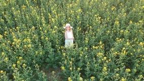 Von der Luft - Fliegen um wenig Mädchen im weißen Kleid und im Hut im Rapsfeld stock video