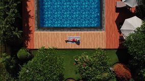 Von der Luft - steigend über die schöne junge Frau, die auf Tuch nahe Swimmingpool im roten Bikini und im Strohhut in den Tropen  stock video