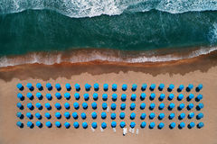 Von der Luftdraufsicht über den Strand Regenschirme, Sand und Meereswellen lizenzfreies stockbild