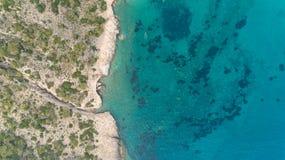 Von der Luftdraufsicht von den Meereswellen Felsen auf dem Strand mit T?rkisMeerwasser schlagend Überraschender Felsenklippenmeer stockfotografie
