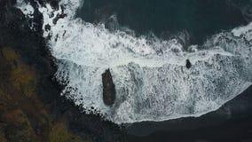 Von der Luftdraufsicht von den Meereswogen, die auf dunklen Felsen auf schwarzem Sandstrand, Kanarische Inseln, Teneriffa, Spanie stock footage
