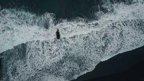 Von der Luftdraufsicht von den Meereswogen, die auf dunklen Felsen auf schwarzem Sandstrand, Kanarische Inseln, Teneriffa, Spanie stock video
