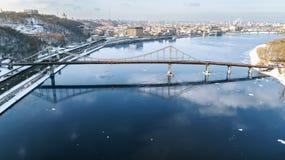 Von der Luftdraufsicht des Fußgängers und des Radfahrenwegwegs auf Parkbrücke im Winter und des Dnieper-Flusses von oben, Stadt v Stockbild