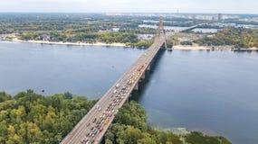 Von der Luftdraufsicht des Moskovskiy-Brückenstraßen-Kraftfahrzeugverkehrstaus vieler Autos von oben, Kyiv-Stadtskyline Lizenzfreie Stockbilder