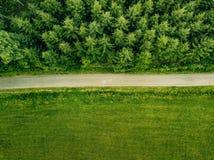 Von der Luftdraufsicht einer Landstraße durch einen Tannenwald und ein grünes Feld im Sommer Stockfotos