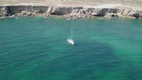 Von der Luftdraufsicht eines Segelboots im blauen Wasser stock footage