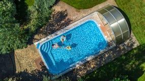 Von der Luftdraufsicht der Familie im Swimmingpool von oben, glückliche Mutter und Kinder schwimmen auf aufblasbaren Ringschaumgu Lizenzfreie Stockfotografie