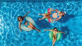 Von der Luftdraufsicht der Familie im Swimmingpool von oben, glückliche Mutter und Kinder schwimmen auf aufblasbaren Ringschaumgu Stockbilder
