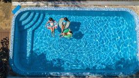 Von der Luftdraufsicht der Familie im Swimmingpool von oben, Mutter und Kinder schwimmen auf aufblasbaren Ringschaumgummiringen u lizenzfreie stockfotos