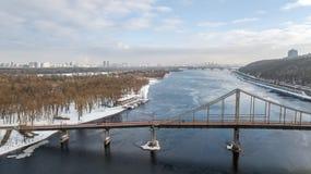 Von der Luftdraufsicht der Fußgängerparkbrücke im Winter und des Dnieper-Flusses von oben, Schnee Kyiv-Stadtbild, Stadt von Kiew- Stockbild