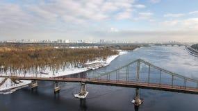 Von der Luftdraufsicht der Fußgängerparkbrücke im Winter und des Dnieper-Flusses von oben, Schnee Kyiv-Stadtbild, Stadt von Kiew- Stockfoto