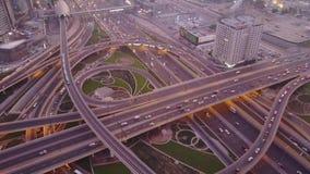 Von der Luftdraufsicht der Landstraßenkreuzung mit Verkehr in Dubai, UAE, bei Sonnenuntergang Berühmte Sheikh Zayed-Straße in Dub stock footage