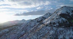 Von der Luftdraufsicht der Seitenbahn über weißen Schneeberg im Winter Forest Woods Snowy-Gebirgsstraßen-Weg establisher Sonnenun stock video