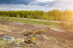 Von der Luftdraufsicht von vier gelben Kettenbaggern, die auf dem Boden nahe der Baustelle stehen und auf den Arbeitstag zu warte stockbilder