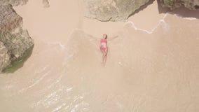 Von der Luftjunge Frau der draufsicht im Bikini, der auf Sandstrand und -Meereswellen liegt Schönheit, die auf Meer ein Sonnenbad stock footage
