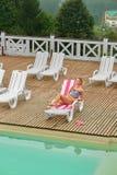 Von der oben genannten Ansicht des Mädchens, entspannend auf Plattformstuhl nahe Pool stockbilder