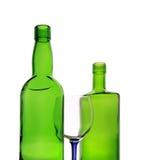 Von hinten beleuchtete Flaschen und Weinglas Lizenzfreie Stockbilder