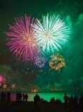 Von hinten beleuchtete Leute, die Feuerwerke Meer betrachtend stehen Stockbild