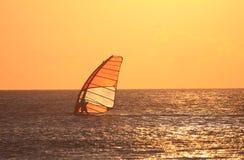 Von hinten beleuchteter Windsurfer am Sonnenuntergang Stockfotografie