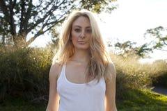 Von hinten beleuchtetes blondes in der weißen Oberseite Stockfotos