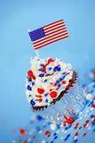 4. von Juli-kleinem Kuchen mit Flagge, besprüht Lizenzfreie Stockfotografie
