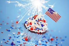 4. von Juli-kleinem Kuchen mit Flagge, besprüht, Wunderkerze Lizenzfreie Stockbilder