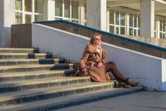 Von mittlerem Alter der tragende modische Mantel und Schuhe der attraktiven Frau, die mit Tasche auf Treppe sitzen, treten vom B? lizenzfreies stockfoto