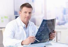 Von mittlerem Alter Doktor, der Röntgenstrahlbild studiert Stockbild