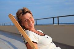 Von mittlerem Alter Frau im Aufenthaltsraum auf Veranda über Meer stockfotos