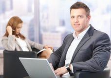 Von mittlerem Alter Geschäftsmann unter Verwendung des Laptops in der Halle Stockbilder