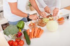Von mittlerem Alter Paare, die eine Mahlzeit vorbereiten stockbild