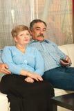 Von mittlerem Alter Paare, die Fernsehhaus überwachen Lizenzfreies Stockbild