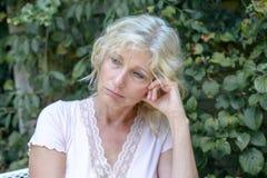 Von mittlerem Alter sitzendes Denken der mutlosen Frau Stockbild