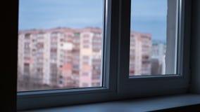 Von Tag zu Nachtansicht durch das Fenster an den Lichtern die Fenster in den hohen Gebäuden stock footage