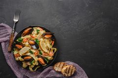 意粉vongole、意大利海鲜面团与蛤蜊和淡菜,在板材用草本和杯白酒在土气石头 图库摄影