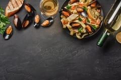 意粉vongole、意大利海鲜面团与蛤蜊和淡菜,在板材用草本和瓶白酒在土气石头 库存照片