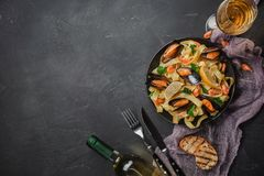 Vongole degli spaghetti, pasta italiana dei frutti di mare con le vongole e cozze, in piatto con le erbe ed il vetro di vino bian immagine stock