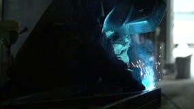 Vonken tegen een donkere achtergrond van lassen De man de lasser in een lusteloze schuur Lasser op het werk in de metaalindustrie stock footage