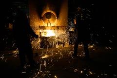Vonken van smeltend staal, Mensen die op fonkelend smeltend staal in oven van gieterij letten royalty-vrije stock foto