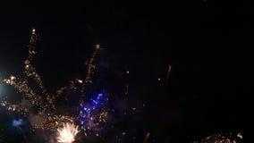 Vonken van vuurwerkkruimeltaart door de nachthemel stock footage