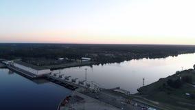 Voo aéreo sobre a central elétrica hidroelétrico no rio do Daugava em Riga no por do sol de nivelamento filme