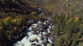 Voo aéreo sobre o rio e a cachoeira raging do vapor na floresta e no vale do outono filme