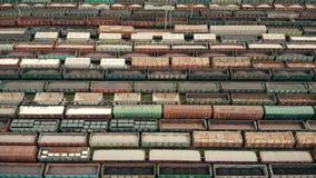 Voo aéreo sobre vagões do frete Vagões coloridos do frete na estação de descarregamento e de carregamento do vagão do frete logís filme