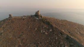 Voo Aero do zangão a uma fortaleza velha com uma ideia do por do sol nas montanhas e no mar vídeos de arquivo