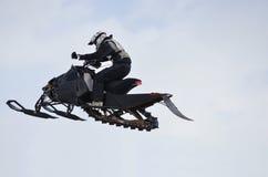 Voo altamente em um cavaleiro do snowmobile de encontro ao céu foto de stock