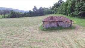 Voo ao lado da casa de campo abandonada velha ao lado da floresta no prado video estoque