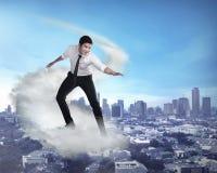 Voo asiático da pessoa do negócio com a nuvem Foto de Stock