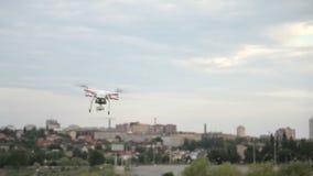 Voo branco do quadcopter do zangão no céu azul no fundo da cidade vídeos de arquivo